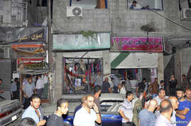 People gather around wreckage after a car bomb exploded in the Jaramana district of southeast Damascus, Aug. 6, 2013.
