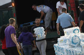 Volunteers unload drinking water from a truck outside Waite High School in Toledo, Ohio, August 3, 2014.