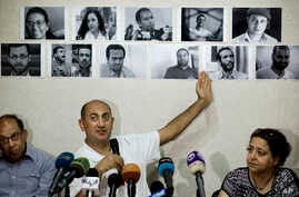 Mideast Egypt Jailed Lawyer: FILE - In this Wednesday, June 22, 2016 file photo, Egyptian lawyer and former presidential candidate Khaled Ali points to photos of jailed activists, who were arrested during protests over two disputed Red Sea islands, i...
