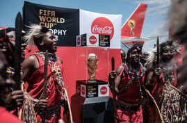 Kenya's Maasai tribe dancers perform upon the arrival of the special aircraft carrying the FIFA World Cup Trophy during its World Tour, Feb. 26, 2018 at the Jomo Kenyatta International airport in Nairobi.