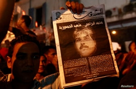 A demonstrator holds up a poster with an image of slain opposition figure Mohamed Brahimi to protest his assassination in Tunis, July 25, 2013.