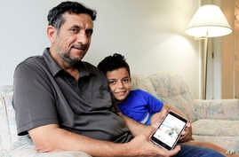 Hadi Mohammed sits with his 9 year old son Mohammed Ghaleb, as he displays a photo of his son as a baby in Baghdad, in their Lincoln, Neb. apartment. Sept. 29, 2018. Death threats drove Hadi Mohammed out of Iraq and to a small apartment in Nebraska,