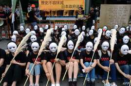 """Taiwanese NGO group members wear masks during a rally to demand that the Japanese government apologize to Taiwanese """"comfort women"""" in Taipei on Aug. 14, 2018."""