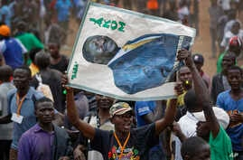 """A supporter of Kenyan opposition leader Raila Odinga holds a banner of him with the Swahili words """"Father"""" and """"Chairman"""" at a rally in the Shauri Moyo area of Nairobi, Kenya, Oct. 18, 2017"""