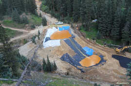 FILE - Yellow mine waste water from the Gold King Mine collects in holding pools in San Juan County, Colorado, Aug. 7, 2015. A contaminated plume of waste water accidentally released from a Colorado gold mine by U.S. environmental agency workers spre