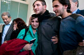 Tawfik Assali, 21, center, of Allentown, Pa., embraces his sister Sarah Assali, 19, upon her and other family members' arrival from Syria at Terminal at John F. Kennedy International Airport in New York, Feb. 6, 2017.