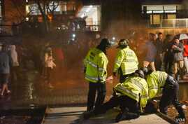 A man is restrained after a post-Super Bowl crowd at the University of Massachusetts Amherst began throwing beer cans and setting off smoke bombs and firecrackers, according to campus police. (Photo Courtesy of Caroline O'Connor/Massachusetts Daily C