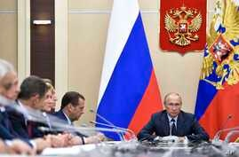 Russian President Vladimir Putin, right, presides over a cabinet meeting at the Novo-Ogaryovo residence outside Moscow, Russia, Sept. 27, 2017.