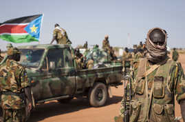 A South Sudanese government soldier stands with others near their vehicles, after government forces on Friday retook from rebel forces the provincial capital of Bentiu, in Unity State, South Sudan, Sunday, Jan 12, 2014.