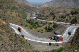 Afghanistan-bound trucks pass through a valley while moving toward the Torkham border crossing in Torkham, Pakistan, Saturday, June 18, 2016.