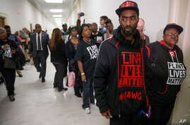 """Flint residents and supporters wear shirts that reads """"Flint Lives Matter"""" as they wait outside the room where Michigan Gov. Rick Snyder and EPA Administrator Gina McCarthy testify before a House Oversight and Government Reform Committee hearing in W"""