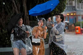 People hold umbrellas against the strong wind caused by tropical storm Pakhar near the waterfront of Victoria Habour in Hong Kong, Aug. 27, 2017.