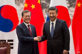 South Korean President Moon Jae-in, left, and Chinese President Xi Jinping shake hands at the end of a signing ceremony at the Great Hall of the People, in Beijing, China, Dec. 14, 2017.