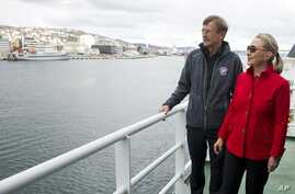 US Secretary of State Hillary Rodham Clinton, right, speaks with Jarle Aarbakke, Rector of the University of Tromso, aboard the Arctic Research Vessel Helmer Hanssen during a boat tour of the coastline with Norway's Minister of Foreign Affairs Jonas