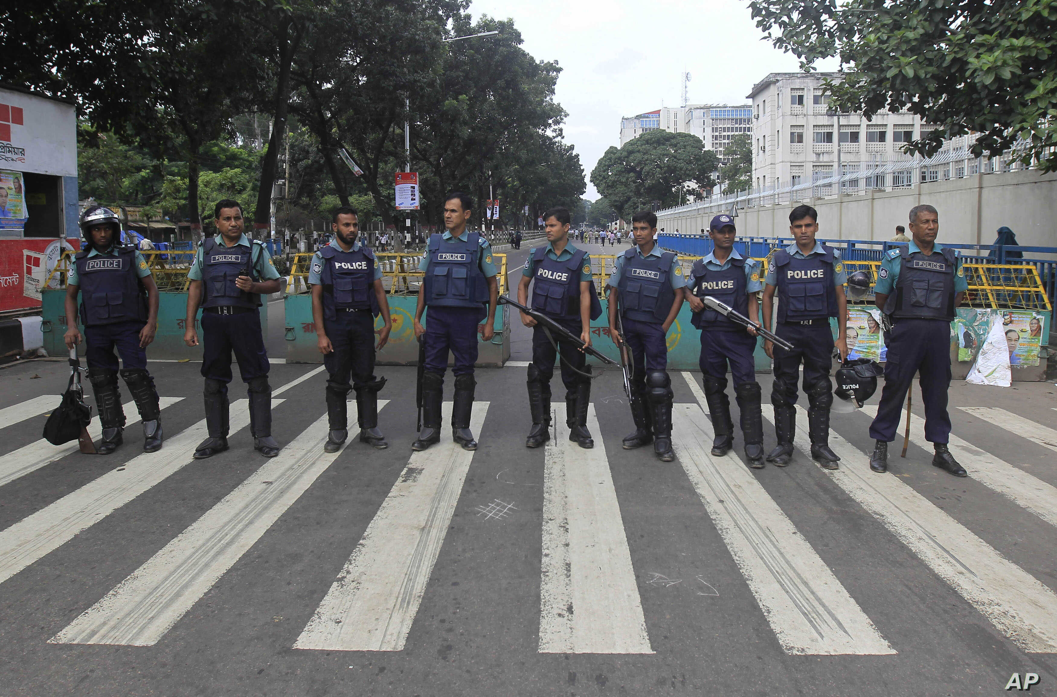 Bangladeshi police officials stand guard on a street during a general strike in Dhaka, Bangladesh, Oct. 27, 2013.