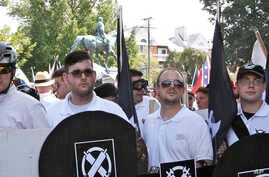 FILE - James Fields, second from left, holds a black shield in Charlottesville, Va., where a white supremacist rally took place, Aug. 12, 2017. Fields was later charged after authorities say he plowed a car into a crowd of people protesting the white