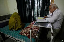 Pakistani psychiatrist Mian Iftikhar Hussain talks to a woman who suffers from severe depression after her cousin was killed by a mortar, at a local hospital in Peshawar, July 3, 2012.