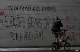 "A cyclist passes graffiti that reads in Portuguese ""Get out Temer and bankers. General elections now!"" at a traffic light at the bus station in Brasilia, Brazil June 12, 2017."