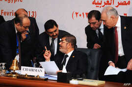 Egyptian President Mohamed Morsi (C) chatting with officials during the closing session of the 12th summit of the Organisation of Islamic Cooperation (OIC) in Cairo, February 7, 2013.