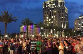 People gather outside the Dr Phillips Center for Performing Art in Orlando for a vigil for the victims and the injured of Orlando nightclub shooting. (S. Dizayee/VOA)
