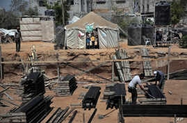 Two Palestinian boys stand outside a tent, background, watching workers rebuild a house which was destroyed during the 2014 summer war between Israel and Hamas, as the long-awaited reconstruction began in Shijaiyah neighborhood eastern Gaza City, Jul