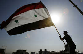 A Syrian protester stands on top of a building as he waves a Syrian flag, during a demonstration against a U.S. raid at a village near the Syrian-Iraqi border, in Damascus, Syria, Oct. 30, 2008. Hundreds of Syrian riot police ringed the shuttered and
