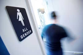 FILE - A bathroom sign welcomes both genders at the Cacao Cinnamon coffee shop in Durham, N.C., May 3, 2016.