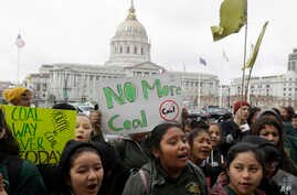 Students yell and hold up signs at a rally for clean energy in San Francisco, Feb. 28, 2018.