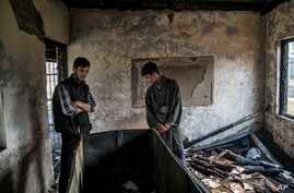 Kashmiri Muslim student Hilal Ahmed Hajam, left, and Nasir Ahmed Mir inspects the damage of a partially burned government high school in Goripora, outskirts of Srinagar, India controlled Kashmir, Tuesday, Nov. 1, 2016. At least 25 schools have been t