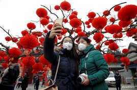 Visitors wearing face masks against pollution take pictures of themselves at the temple fair at Ditan Park (the Temple of Earth) as the lunar new year of the rooster is celebrated, in Beijing, China, Jan. 28, 2017