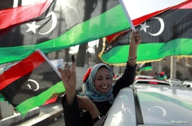 A woman celebrates on the streets in Tripoli's Martyrs Square after casting her vote during Libya's National Assembly election, July 7, 2012.
