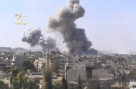 This image taken from video obtained from the Ugarit news network, which has been authenticated based on its contents and other AP reporting, shows smoke rising from the city following heavy bombing from military warplanes, in Deir el-Zour's Jbeileh