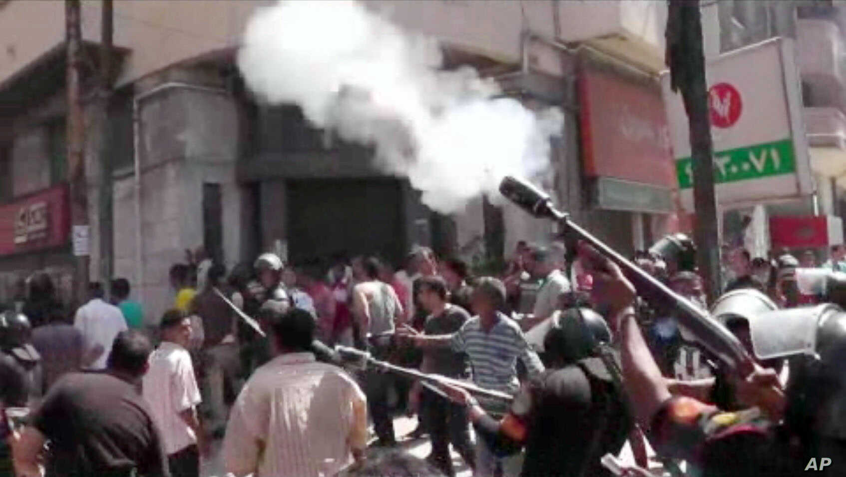 An image made from video shows police firing tear gas at supporters of ousted President Mohammed Morsi in Alexandria, Egypt, Aug. 14, 2013.