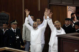 FILE - Cleric Safwat Hegazi (c), and Muslim Brotherhood leader Mohammed el-Beltagy (r) with other defendants gesture during an appearance in a courtroom in Cairo, Egypt.