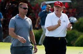 FILE - President Donald Trump walks with Gene Gibson, commanding officer at Coast Guard Station Lake Worth Inlet, as he arrives, Dec. 29, 2017, to meet with members of the U.S. Coast Guard, who he invited to play golf, at Trump International Golf Clu