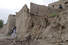 Man clears rubble after part of his house collapsed during an earthquake, Jalalabad, Afghanistan, Oct. 26, 2015.