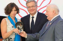 Zhanna Nemtsova, left, the daughter of slain Russian opposition leader Boris Nemtsov  stands together with Poland's President Bronislaw Komorowski  center, and former president. Lech Walesa, right, after receiving Poland's 4 million zlotys ( US $1 mi