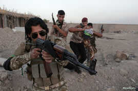 FILE - Shi'ite volunteers, who have joined the Iraqi army to fight against the predominantly Sunni militants from the radical Islamic State of Iraq and the Levant (ISIL), take part in a military-style training in Basra, Iraq.