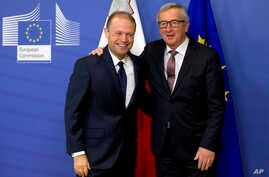 European Commission President Jean-Claude Juncker, right, welcomes Malta's Prime Minister Joseph Muscat prior to a meeting at EU headquarters in Brussels on Wednesday, Nov. 16, 2016. Malta will assume the EU rotating six month presidency as of Jan. 1