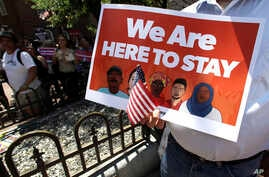 """A protester holds a sign during a """"Here to Stay"""" rally at the Irish Famine Memorial in Boston, July 6, 2017. U.S. lawmakers have introduced legislation to all a path to citizenship for immigrants brought into the U.S. as children."""