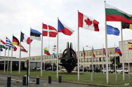 FILE - In this 2007 file photo, NATO member country flags are seen outside NATO headquarters in Brussels. A spokeswoman on Sunday, June 24, 2012 said NATO's governing body will meet Tuesday, June 26, 2012 to discuss the Syrian downing of a Turkish pl