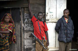 FILE - Congolese fighters from the Mai-Mai militia stand outside a hut in the village of Kalenge in eastern Congo, Feb. 4, 2009.