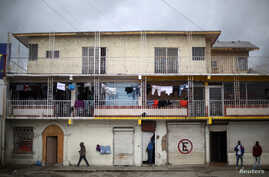 People walk past a building where Haitian migrants rent apartments in Tijuana, Mexico, Feb. 26, 2017.