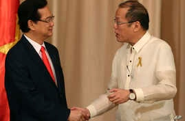 Philippine President Benigno Aquino III, right, shakes hands with Vietnamese Prime Minister Nguyen Tan Dung after their joint press statement at the Malacanang Presidential Palace in Manila, Philippines, May 21, 2014.