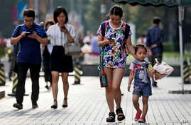 Pedestrians view their smartphones as they walk along a sidewalk in Beijing, Aug. 9, 2017. China has become one of the world's largest mobile phone markets as the phones grow more popular among all age groups in China.