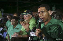 Andrew Holness (R), leader of the opposition Jamaican Labour Party, speaks to supporters at the party headquarters after they won the general election in Kingston, Jamaica, Feb. 25, 2016.