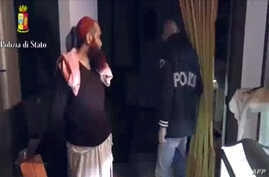 This screen grab taken from a video released on April 24, 2015 by the Italian police shows a man (L) suspected to be a member of an armed organization inspired by al-Qaida and other radical organisations.