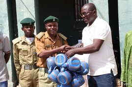 Pastor Yohanna Buru, founder of the Peace, Revival and Reconciliation Foundation, hands the organization's donation to a prison officer at Kaduna Central Prison.