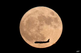 A jet plane flies across the moon seen from Beijing, China, Nov. 14, 2016. The brightest moon in almost 69 years lights up the sky on Monday in a treat for star watchers around the globe.
