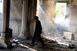 An Egyptian walks among the burned remains of the Rabaah al-Adawiya mosque, in the center of the largest protest camp of Morsi supporters that was cleared by security forces, Nasr city, Cairo, August 15, 2013.